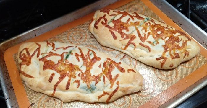 two spinach calzones on a baking sheet
