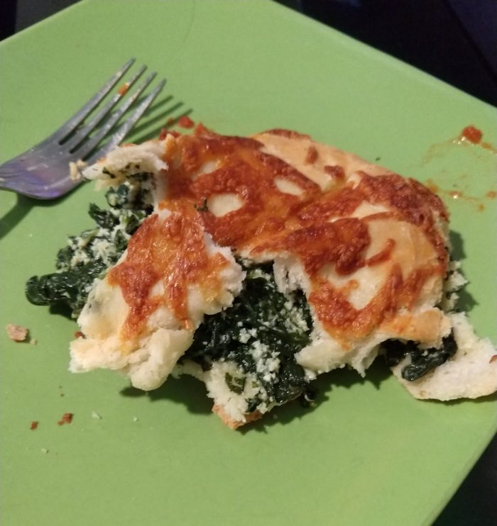 a plate with a partially eaten piece of calzone. It has a thick layer of spinach in the middle and I have picked away at the bread on the outside