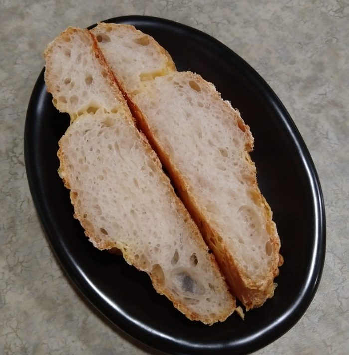 a small black plate with two slices of Gruyère-Stuffed Crusty Loaves, showing the airy crumb inside
