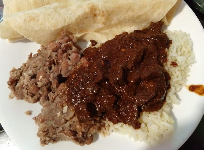 a plate of chili colorado on rice, with beans and tortillas