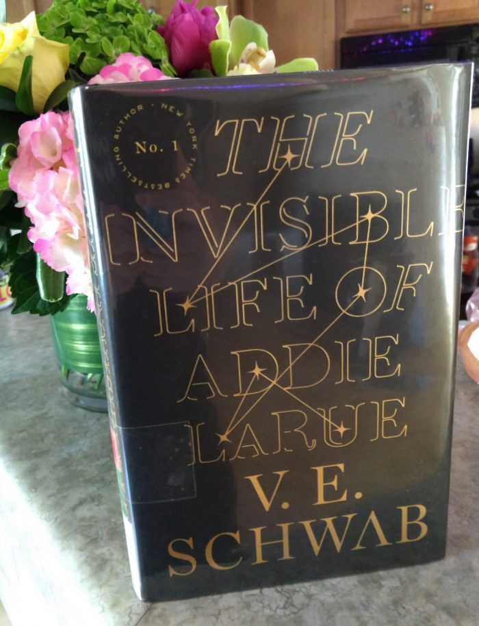 hardback book: The Invisible Life of Addie LaRue, set in front of a boquet of flowers