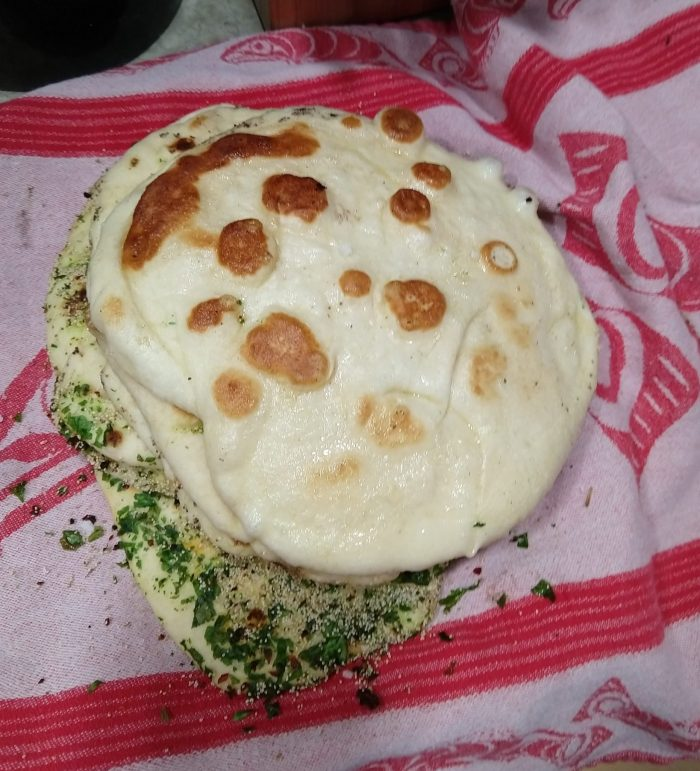 a stack of round naan breads on a towel. Some are plain and some are covered in herbs and seeds