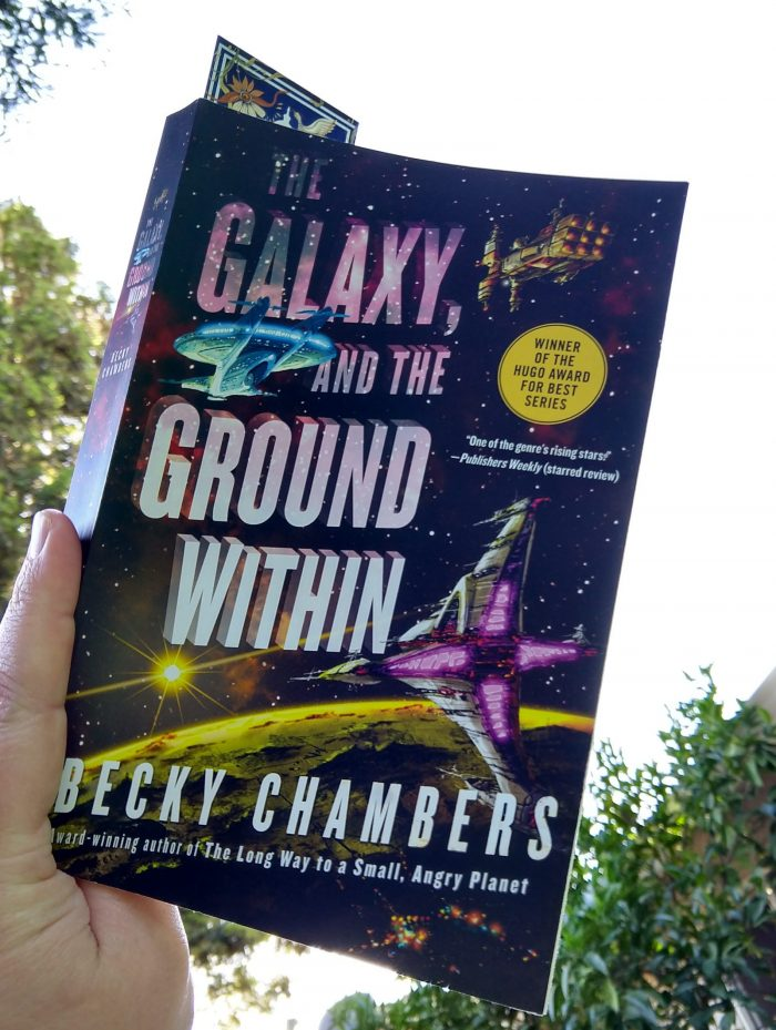 paperback book: The Galaxy, and the Ground Within by Becky Chambers. Photo taken in my backyard