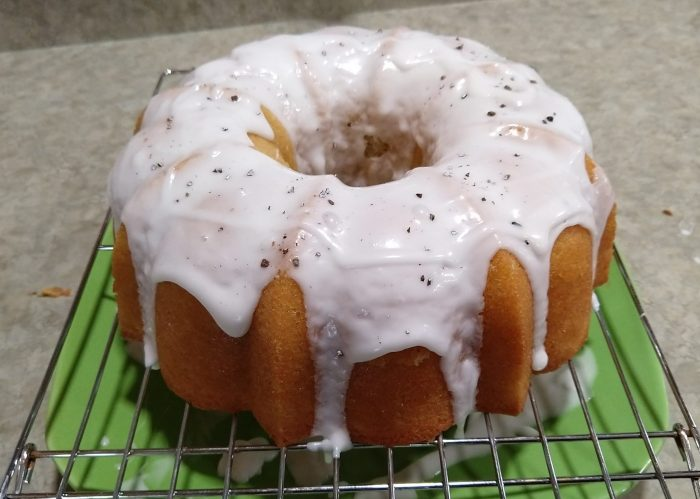 a golden bundt cake dripping with coconut glaze. The cake is on a wire rack and there's a plate underneath to catch the glaze