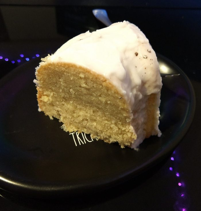 a slice of coconut cardamom bundt cake on a small black plate. The cake is dense and moist