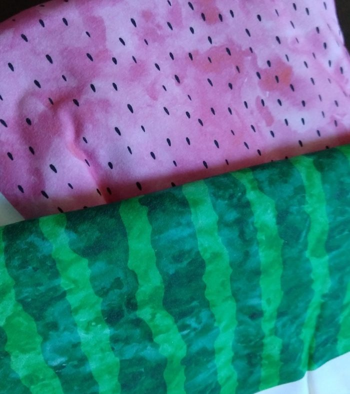 two folded pieces of fabric, both with a watercolor-style pattern. One is light pink with black seeds like the inside of a watermelon and one has light and dark green stripes like a watermelon rind