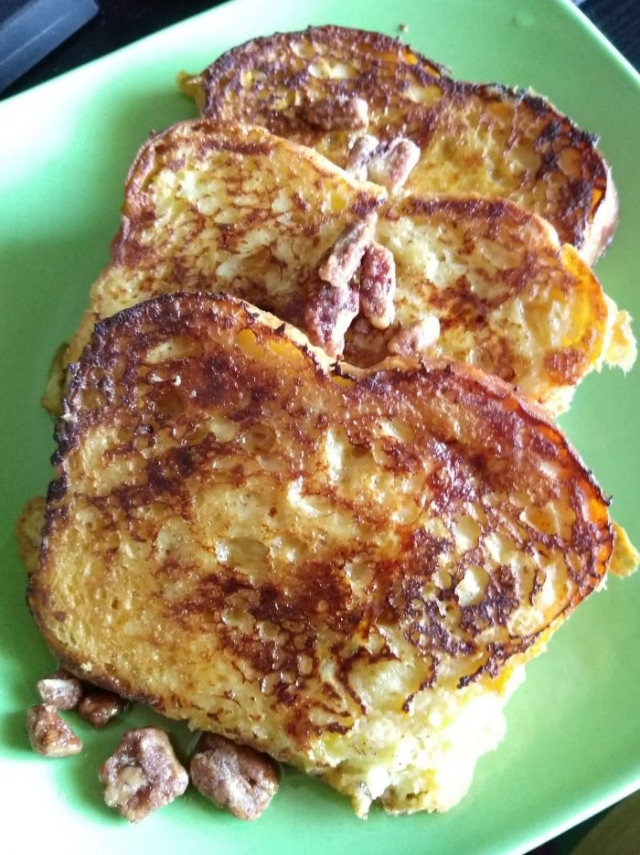 a plate of three slices of brioche french toast topped with syrup and pecans