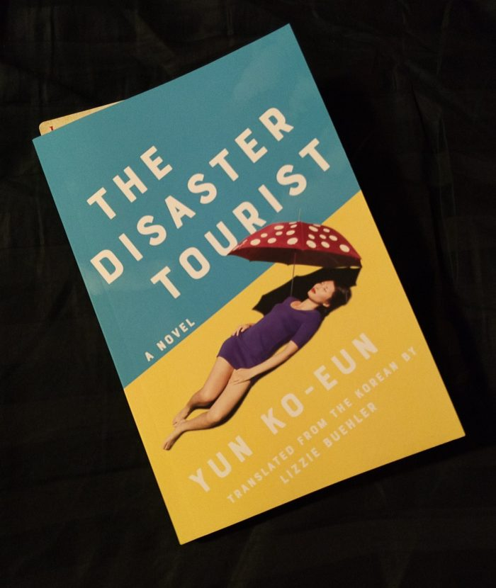 The Disaster Tourist by Yun Ko-Eun. Cover is blue and yellow with a woman lying down inder a parasol