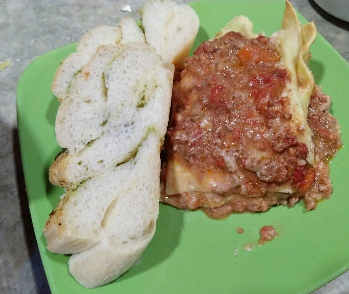 a plate with a piece of lasagne and a piece of bread, which shows the cross-section of twists inside the loaf