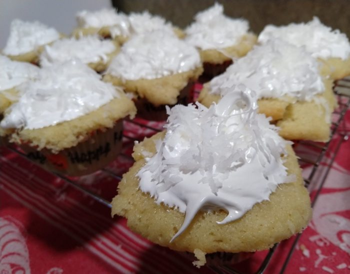 12 coconut cupcakes on a wire rack, the focus is on the corner of the rack with the rest a little blurry. The cupcakes are topped with a dollop of meringue and shredded coconut