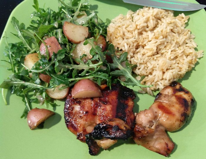 a plate of grilled chicken thighs, rice pilaf, and an arugula and roasted potato salad