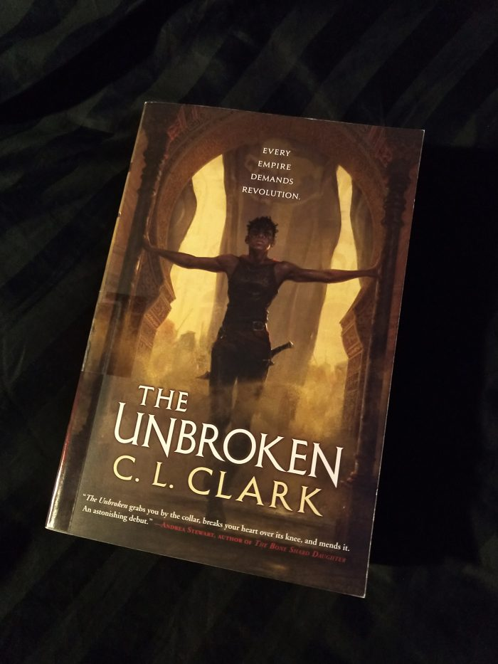 paperback book: The Unbroken by C.L. Clark. Cover image is a woman with wiry muscles and a sword at her hip emerging from a battle