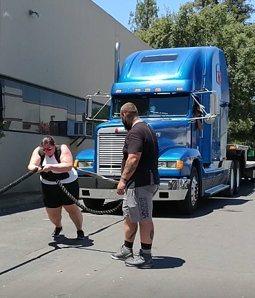 me, wearing a harness attached to a semi truck, leaning foward and holding a guide rope, attempting to move the truck forward with my body