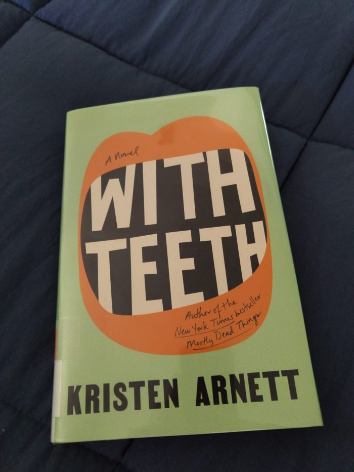 hardback book: With Teeth. Cover is light green. There is a stylized mouth wide open and the title of the book is inside to look like teeth
