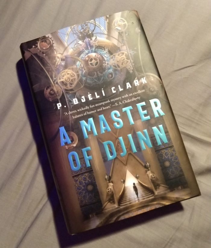 hardback book A Master of Djinn. Cover features a steam-punk style device and the sillhouette of a woman walking up stairs