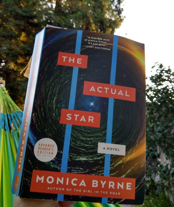 paperback book: The Actual Star. The cover looks like you're looking up through a hole in a cave to see a star in the sky. Photo taken outside in my hammock