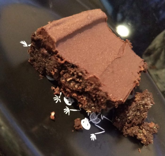 a square piece of zucchini brownie, topped with a chocolate ganache, on a small black plate