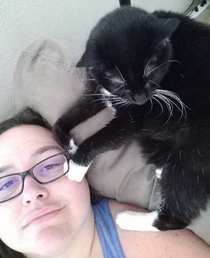 I'm lounging on the couch, head up to the ceiling, Huey the cat is on top of hte couch, her front paws touching my face and a back foot on my shoulder