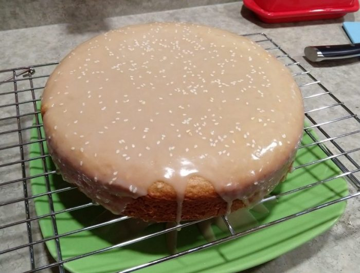 One round layer of cake on a wire rack, covered in tahini glaze that is dripping down the sides, topped with seasame seeds