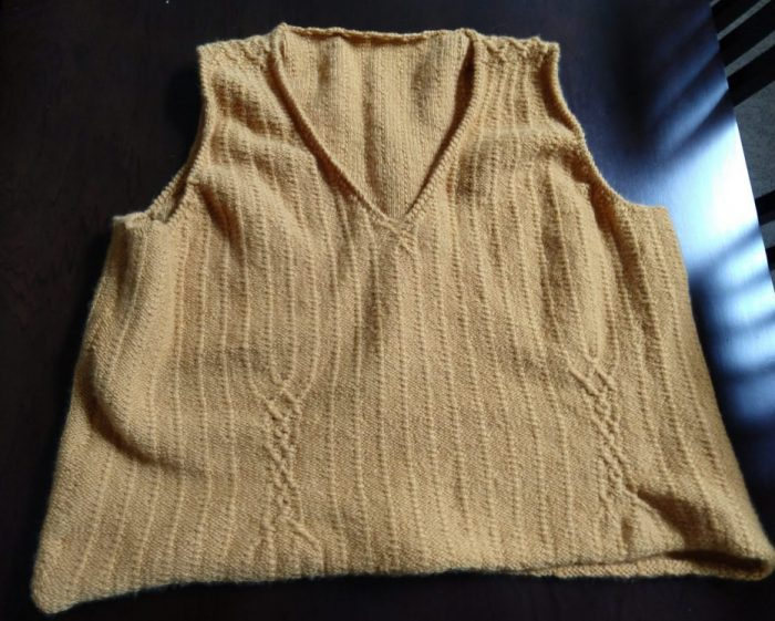 a hand-knitted, yellow sweater vest. This is a picture of the front, featuring a v-neck and two columns of cables