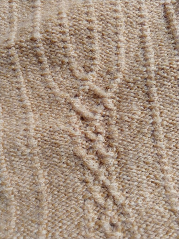 a hand-knitted, yellow sweater vest. This is a close-up of the cable detail on the front