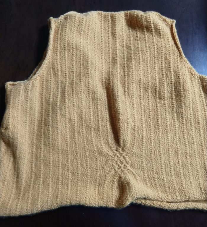 a hand-knitted, yellow sweater vest. This is the back, which has one cable section in the low back to bring in the vest and define the waist