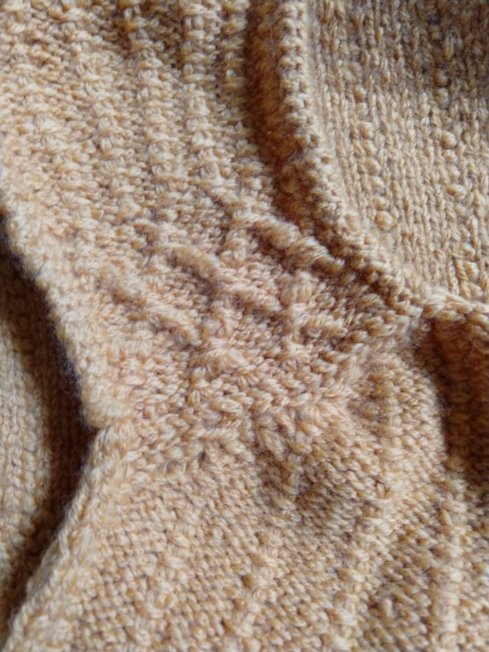 a hand-knitted, yellow sweater vest. This shows the cable detail in the shoulder and the seam between the front and back sides (three-needle bind off)