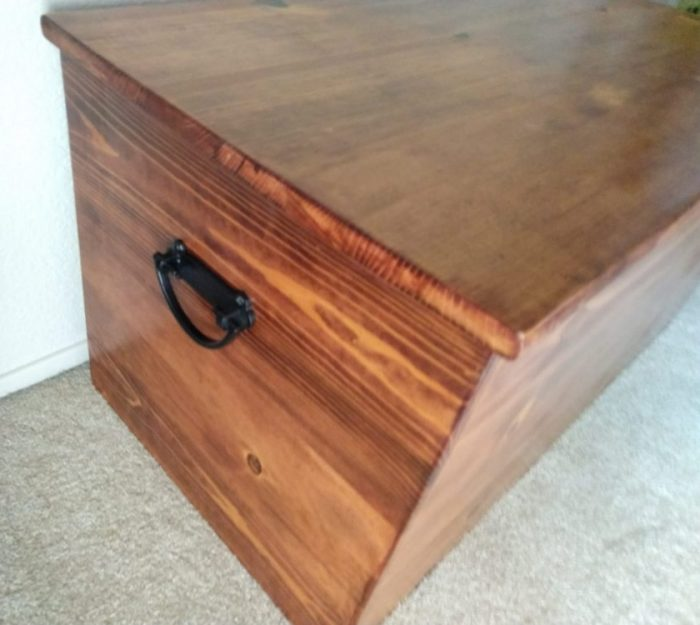 side view of my new cedar-lined chest showing a black handle and the grain of the wood
