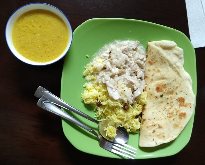 a plate of naan bread, saffron rice pilaf, and moghul braised chicken, with a small bowl of lentils with garlic butter to the side.