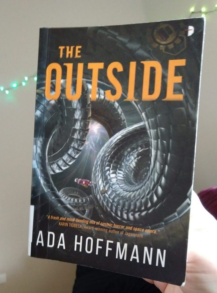 Paperback book: The Outside by Ada Hoffman. The cover features big, twisty metal tentacle-looking things and a tiny person in a space suit standing on one