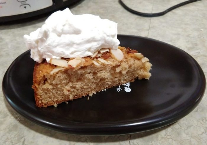 a slice of spiced honey cake on a small black plate, topped with a generous amount of whipped cream
