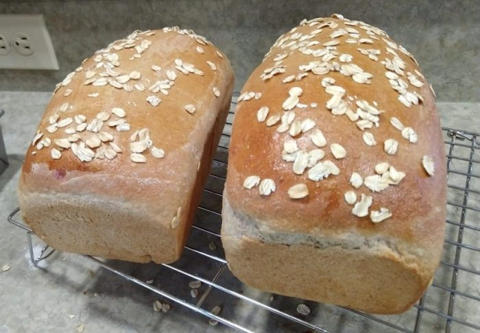 two loaves of honey oat bread on a wire rack. The loaves are topped with a festive sprinkling of rolled oats