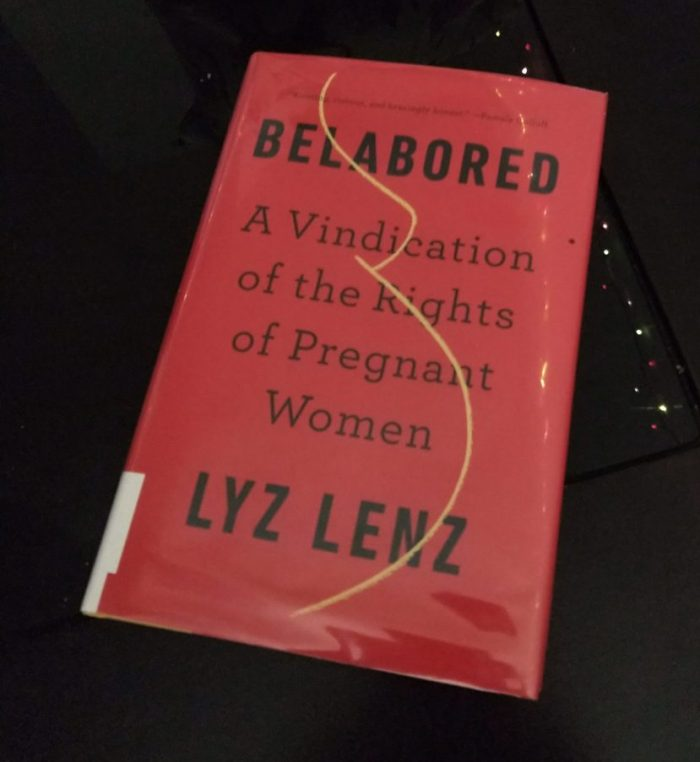 hardback book with a red cover and a stylized yellow outline of a pregnant boob and belly. Belabored: A vindication of the rights of pregnant women
