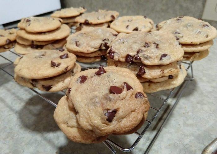 some very flat chocolate chip cookies piled on a wire rack