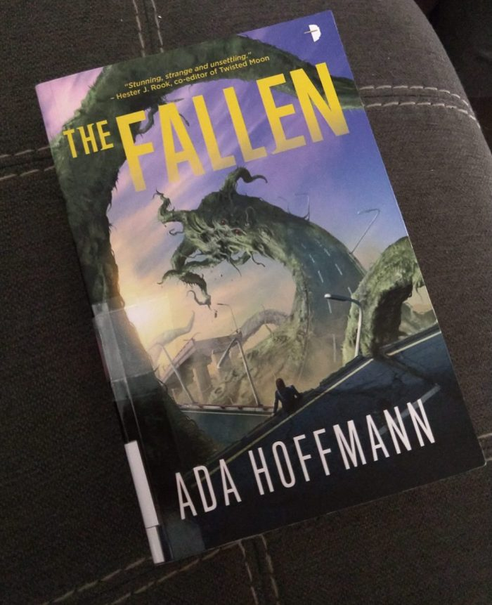 paperback book featuring a lovecraftian-style monster and a destroyed freeway. The Fallwen by Ada Hoffman