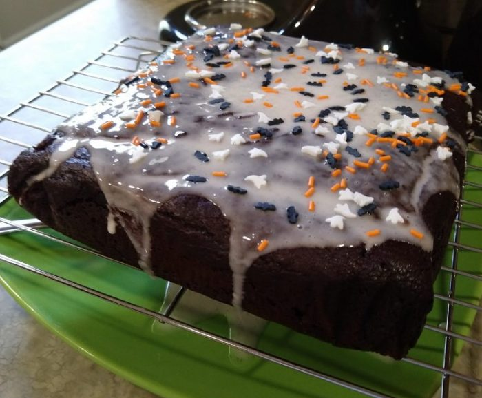 a square chocolate cake topped with vanilla glaze and halloween sprinkles